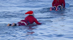 Santa Claus paddles out to go surfing. Stock Footage