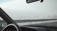 Driving a car on a highway in harsh winter. View from inside to frosty fields. Stock Footage