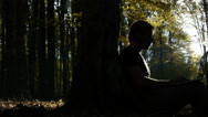 Man in nature park sitting under a tree and typing on laptop Stock Footage