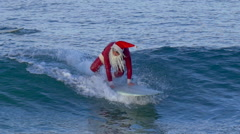 Santa Claus does a hang five trick and then wipes out while surfing. Stock Footage