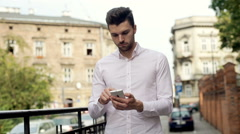 Stylish man standing on the street in the city and texting on smartphone Stock Footage