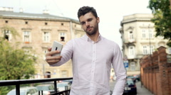 Handsome, stylish man standing in the city and doing selfies on smartphone Stock Footage