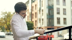 Man doing notes in journal while speaking with someone through cellphone Stock Footage