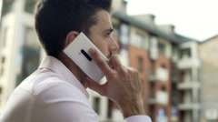 Man looking absorbed while talking on cellphone in the city Stock Footage