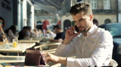 Absorbed man browsing internet on tablet while chatting on cellphone Stock Footage