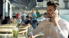 Man answers cellphone while sitting in the outdoor cafe and drinking mojito Stock Footage