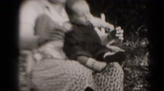 1947: woman holds closely small baby on her lap as it smiles. MIDDLETOWN Stock Footage