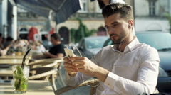Absorbed man listening music and browsing internet on smartphone Stock Footage