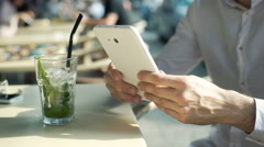 Man browsing internet on tablet and drinking refreshing mojito Stock Footage