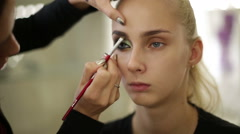 Makeup artist paints one eye of the model Stock Footage
