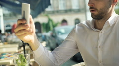 Man looking absorbed while browsing internet on smartphone Stock Footage