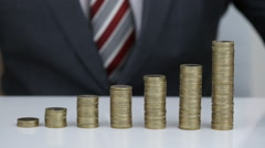 Businessman Putting Coin On Stack Of Coins Stock Footage