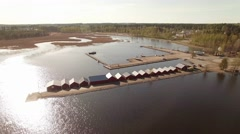 Boathouses at a small harbor in Kerimaki, Finland. Aerial overflight shot Stock Footage
