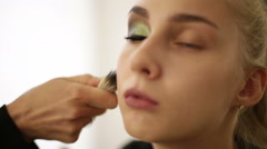 Makeup artist deals powder on the model's face Stock Footage