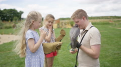 4K Children at a falconry centre with little girl handling a peregrine falcon Stock Footage