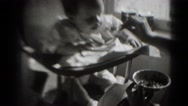 1947: young baby being fed by his mother in high chair next to window MIDDLETOWN Stock Footage