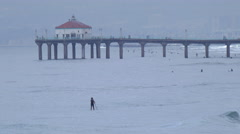 A man stand-up paddleboards sup near the Manhattan Beach Pier. Stock Footage