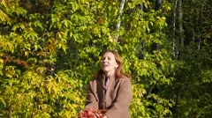 The girl throws the leaves over the head in the Park Stock Footage