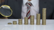 Businessman Looking Coins Stack Through Magnifier Stock Footage