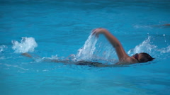Healthy boy back stroke swims slow motion in swimming pool Stock Footage