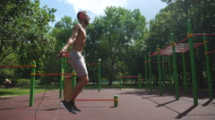 Sportman man jumping rope on green lawn park Stock Footage