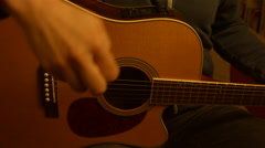 An anonymous man strumming an acoustic, western-style guitar, captured in 4K Stock Footage