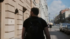Handsome man with a beard exploring a city, wearing black backpack, looking Stock Footage