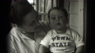 1947: baby in penn state t-shirt smiles and happily waves at the camera Stock Footage