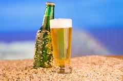 Ice cold green unlabelled bottle of beer in the beach concept Stock Photos