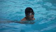Healthy boy breast stroke swims slow motion in swimming pool Stock Footage
