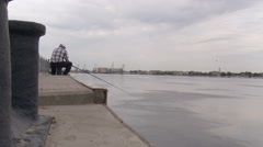 Volga River. Concrete River Bank. Man Sitting, Fishing. Cloudy Summer Day. Grey Stock Footage