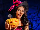 Woman wearing witch hat holding big pumpkin. Stock Photos