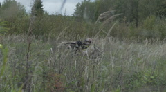 Soldier with weapon in hand goes on the grass. Military moves through the field Stock Footage