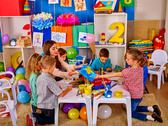 Children with teacher woman painting on paper in kindergarten . Stock Photos