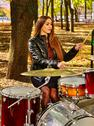 Woman drummer playing drum in autumn park. Stock Photos