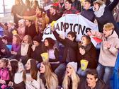 Sport fans holding champion banner on tribunes. Stock Photos