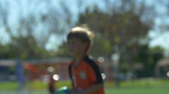 A boy does a throw-in of the ball while playing youth soccer football. Stock Footage