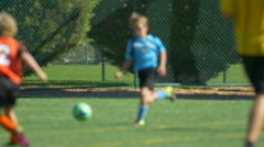 Details of a ball and boys legs playing youth soccer football on a turf field. Stock Footage