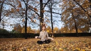 Young woman playing with leaves in autumn park. Theme of holidays, vacation Stock Footage