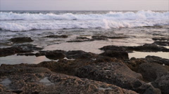 Waves breaking against rocks on sea shoreline. Stock Footage
