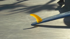 A blue longboard surfboard with a yellow fin. Stock Footage