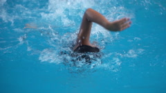 Healthy boy front crawl swims slow motion in swimming pool Stock Footage