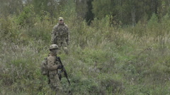 Two military standing in the field and talk with a gun in his hand Stock Footage