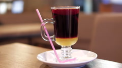 A cup of hot mulled wine on a table with pink straw Stock Footage