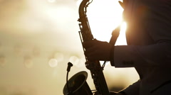 The musician playing the saxophone at sunset3 Stock Footage