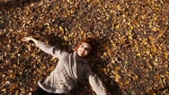 Smiling happy girl portrait, lying in autumn leaves. Outdoor Stock Footage