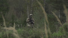 Soldier with a gun in his hand on a hill in a forest Stock Footage