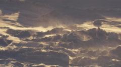 Slow motion - ground blizzard on broken snow golden light Stock Footage