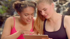 Girls searching internet on tablet outdoor. Close up of friends surfing internet Stock Footage