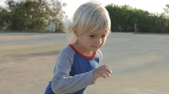 Steadycam shot of child skateboarding on helipad in park Stock Footage
